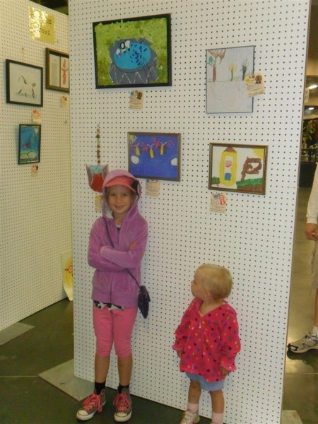 Here is Anna under two of her pieces of artwork at the county fair!  The blue one with butterflies and the one of the pool above that.  So proud of her!  She's proud of her too!